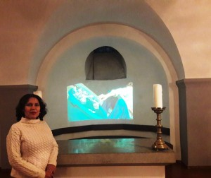 Margarita Grullón, curadora de la exposición Kunst und Religión, junto al video Dilución de Jochi Muñoz